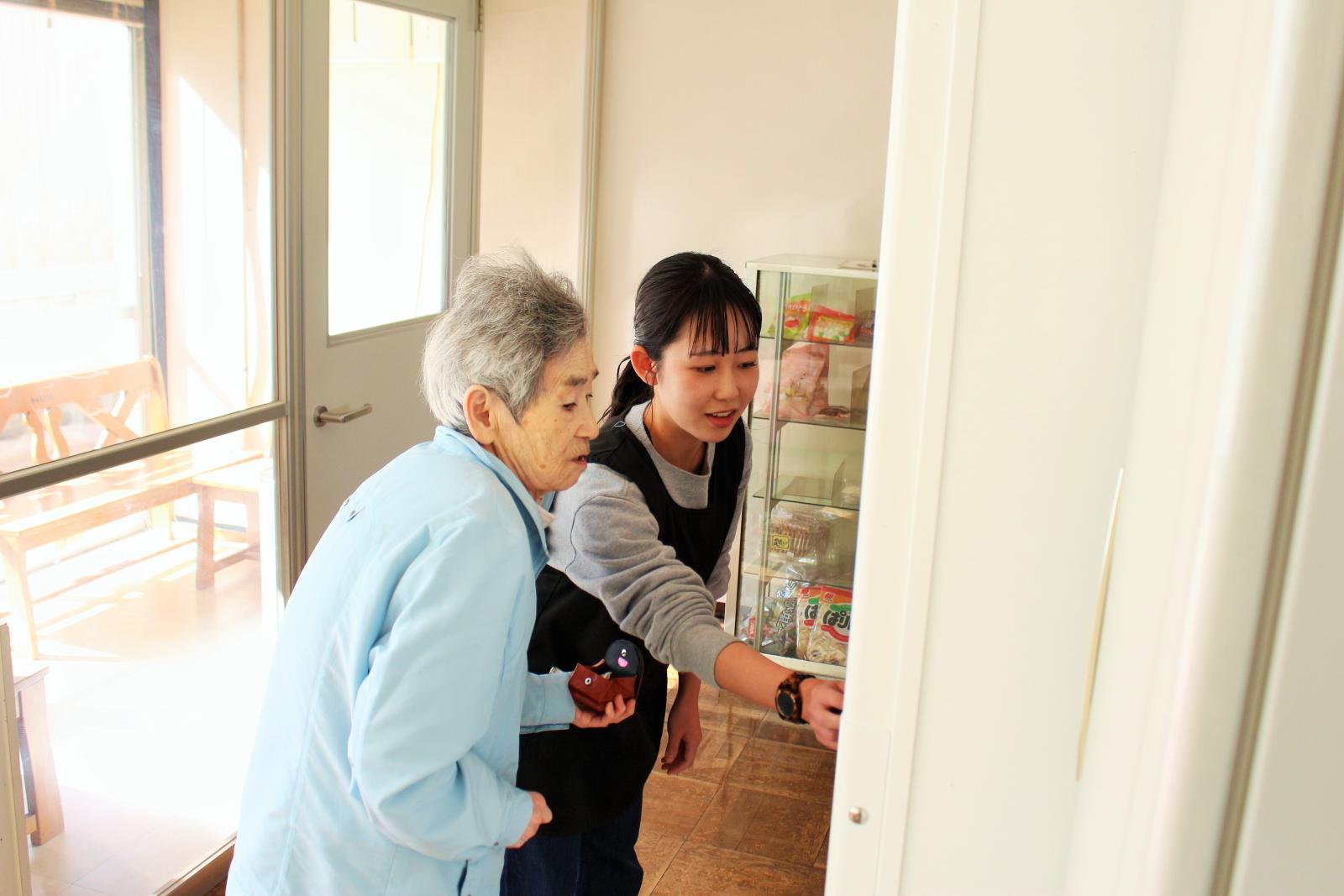 自動販売機での買い物の手伝いをする学生